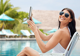 Frau liest ePaper im Urlaub